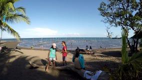 Crianças dos povos na maior parte que têm o divertimento que fica na praia durante o verão quente video estoque