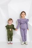 Crianças, duas irmãs 1 5 e 5 anos velho nos trajes idênticos de cores diferentes, meninas em um branco Fotos de Stock Royalty Free