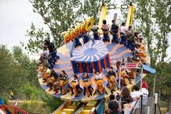 Crianças e adultos que montam o passeio do parque de diversões fotos de stock royalty free