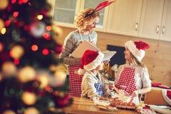 Crianças e mãe do tempo da família que fazem cookies Imagem de Stock
