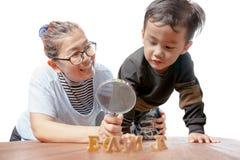Crianças e mãe que aprendem junto com o em da felicidade das famílias foto de stock