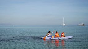 Crianças e mãe que kayaking na praia filme