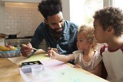 Crianças e mesa de cozinha de Painting Picture On do pai foto de stock royalty free