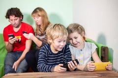 Crianças e pais que jogam jogos em smartphones Fotos de Stock Royalty Free