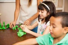 Crianças e professor em uma classe esculpindo fotografia de stock royalty free