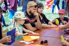 Crianças e seus pais que participam em artes e em oficina do ofício fora foto de stock royalty free