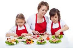 Crianças e sua mãe que preapring os sanduíches do partido imagens de stock