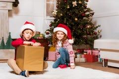 Crianças em chapéus de Papai Noel com presente Imagens de Stock