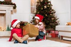 Crianças em chapéus de Papai Noel com presente Fotografia de Stock