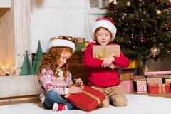 Crianças em chapéus de Papai Noel com presentes Fotos de Stock