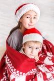 Crianças em chapéus de Santa perto da árvore de Natal, espera por feriados imagens de stock royalty free