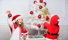 Crianças em chapéus de Santa que decoram a árvore de Natal Conceito da tradição da família Crianças que decoram a árvore de Natal imagem de stock