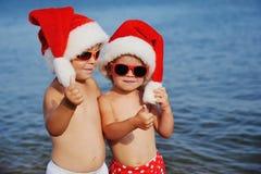 Crianças em chapéus do Natal contra o mar Foto de Stock Royalty Free