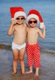 Crianças em chapéus do Natal contra o mar Fotografia de Stock