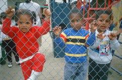 Crianças em idade pré-escolar afro-americanos em um campo de jogos Fotos de Stock