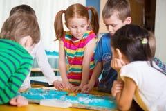 Crianças em idade pré-escolar bonitos que plaing o jogo na tabela Fotografia de Stock Royalty Free