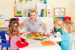 Crianças em idade pré-escolar com o professor fotografia de stock royalty free