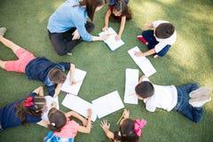 Crianças em idade pré-escolar que tomam uma classe fora Imagens de Stock