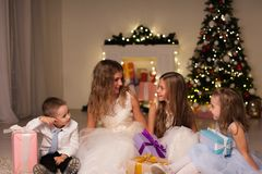 Crianças em presentes do ano novo dos chuveirinhos do Natal imagens de stock