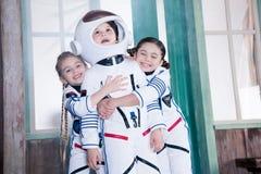 Crianças em trajes do astronauta, meninas que abraçam o menino Fotos de Stock Royalty Free