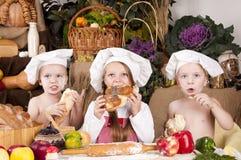 Crianças em um cozinheiro chefe \ 'em chapéus de s que comem o pão Fotos de Stock Royalty Free