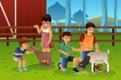Crianças em um jardim zoológico de trocas de carícias Fotos de Stock