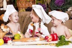 Crianças em um sorriso dos chapéus do cozinheiro chefe \ 'do s Fotos de Stock Royalty Free