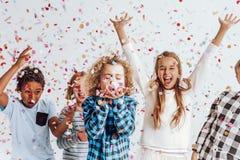 Crianças em uma sala completamente dos confetes foto de stock royalty free