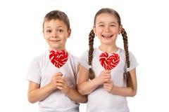 Crianças engraçadas com o coração dos pirulitos dos doces isolado no branco Dia do `s do Valentim Imagem de Stock