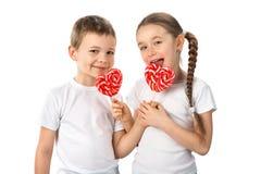 Crianças engraçadas com os pirulitos vermelhos dos doces na forma do coração isolados no branco Dia do `s do Valentim Fotografia de Stock Royalty Free