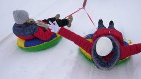 Crianças engraçadas em revestimentos vermelhos no passeio do inverno através da neve em trenós e uma tubulação inflável da neve e video estoque
