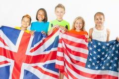Crianças engraçadas que guardam a bandeira Grâ Bretanha e a bandeira nacional americana Fotos de Stock Royalty Free