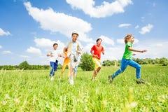 Crianças entusiasmado que jogam e que correm no campo Fotografia de Stock Royalty Free