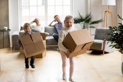 Crianças entusiasmado que jogam guardando caixas após mover-se na casa nova imagem de stock royalty free