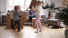 Crianças entusiasmados que correm as caixas levando que têm o divertimento na casa nova vídeos de arquivo