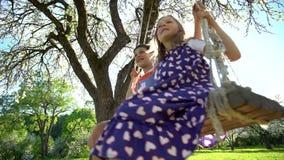 Crianças europeias felizes pequenas que sorriem alegremente ao balançar filme
