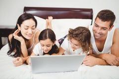 Crianças felizes com os pais que usam o portátil na cama imagens de stock royalty free