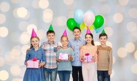 Crianças felizes com os presentes na festa de anos Fotos de Stock Royalty Free