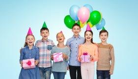 Crianças felizes com os presentes na festa de anos Fotografia de Stock Royalty Free