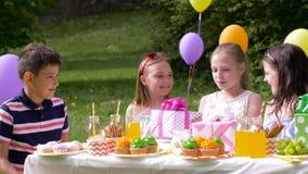 Crianças felizes com os presentes na festa de anos no verão filme