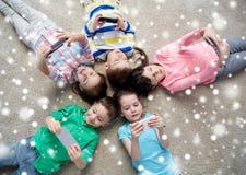 Crianças felizes com os smartphones que encontram-se no assoalho Fotografia de Stock