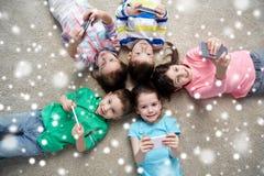 Crianças felizes com os smartphones que encontram-se no assoalho Fotografia de Stock Royalty Free