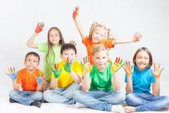 Crianças felizes com sorriso pintado das mãos Fotos de Stock