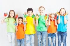 Crianças felizes com sorriso pintado das mãos Fotografia de Stock Royalty Free