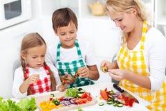 Crianças felizes com sua mãe na cozinha, clos da vista superior imagens de stock