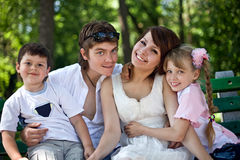 Crianças felizes da família e do grupo no banco no parque. Fotos de Stock Royalty Free