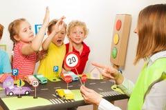 Crianças felizes espertas que estudam regras do regulamento de tráfego Fotos de Stock