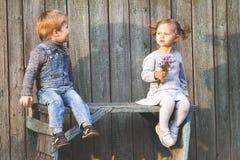 Crianças felizes exteriores no outono, sentando-se no banco Primeira data Fotos de Stock Royalty Free
