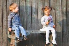 Crianças felizes exteriores no outono, sentando-se no banco Primeira data Imagens de Stock Royalty Free