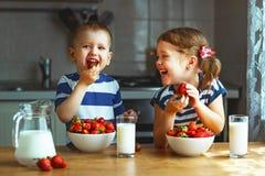 Crianças felizes irmão e irmã que comem morangos com leite imagens de stock royalty free